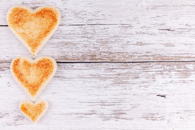 Поджаренный хлеб сердца на деревянный стол, концепция завтрака в счастливой семье