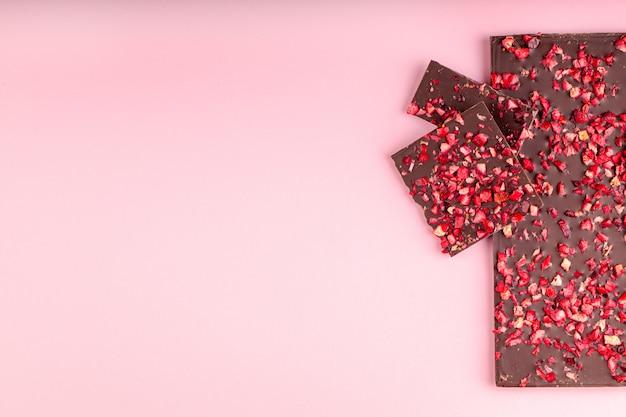 乾燥イチゴの部分とチョコレートはピンクの背景のスタックにあります。