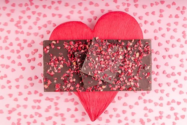 乾燥ベリーの部分とチョコレートは赤いハートのスタック