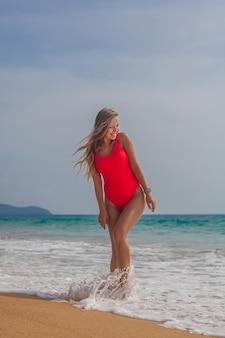 Сексуальная женщина в красном купальнике на пляже