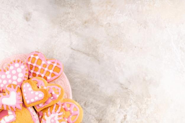 バレンタインデーのための自家製の艶をかけられた装飾されたハート型のクッキーのプレート
