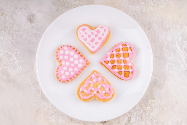 手作りの艶をかけられたクッキーと白いプレート