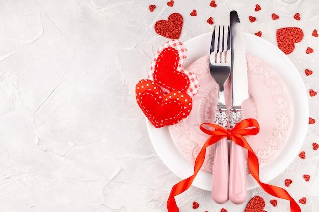 Белые и розовые тарелки с вилкой, ножом и бантиком из красной ленты с декоративными сердечками