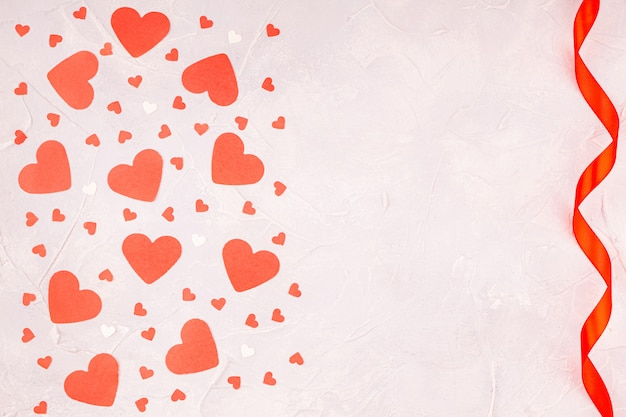 コンクリートグレーの赤いリボンと紙吹雪の紙の心