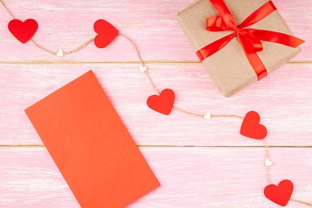 リボンリボン、赤いバレンタインブランクカード、ジュートロープ上の心のギフトボックス