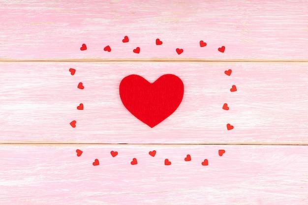 センターで赤いハートとピンクの木製の背景に小さな紙吹雪心
