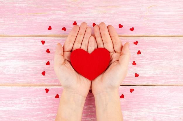 赤い紙吹雪心とピンクの木製の背景に赤いハートを保持している女性の手