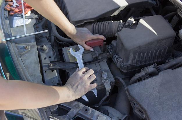 ボンネットの下の車のバッテリーの修理、女性の手の車の修理