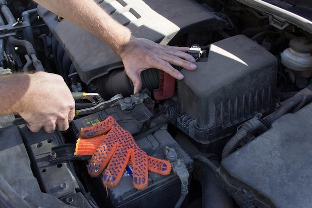 Механик на работе, крупным планом детали двигателя автомобиля под открытым капотом.