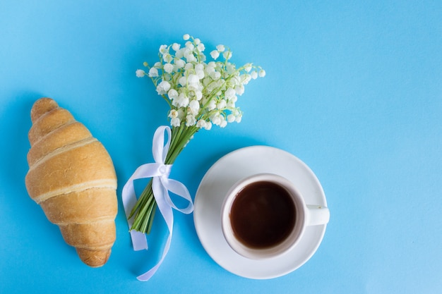 スズランの花の花束とコーヒーマグカップとメモおはよう、美しい朝食、平面図、フラットレイアウト。クロワッサンとコーヒー