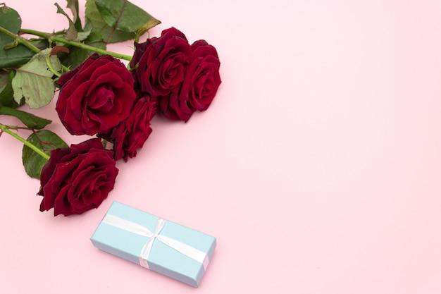 ピンクの背景にギフトブルーボックスと赤いバラ