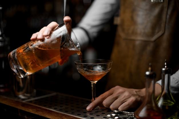 バーテンダーがストレーナーからアルコールカクテルを注ぐ