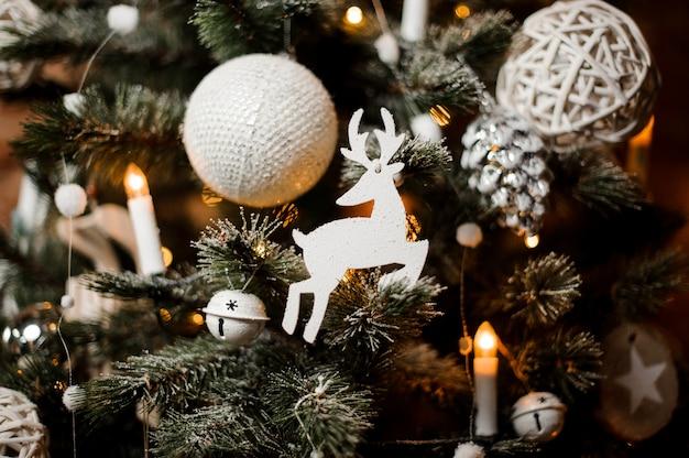 雪とおもちゃで飾られた美しいクリスマスツリーの枝