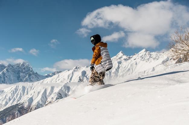 山の斜面に乗ってスポーツウェアの女性スノーボーダー