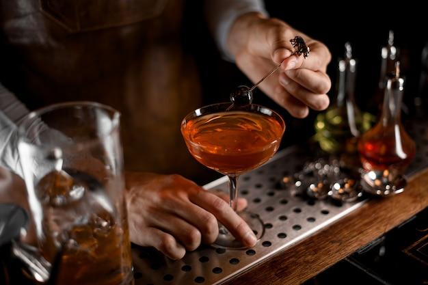 Бармен кладет оливковое в бокал с коктейлем