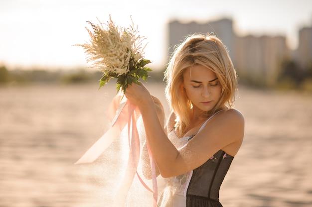 手に花を持つ魅力的な金髪の女性
