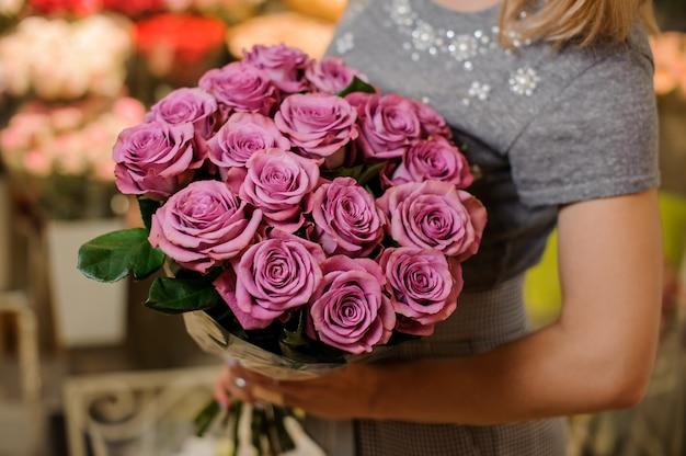 紫色のバラの美しい花束を保持している女性