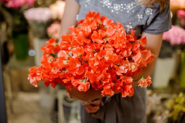 花の美しい明るいオレンジ色の花束を保持している灰色のドレスの花屋