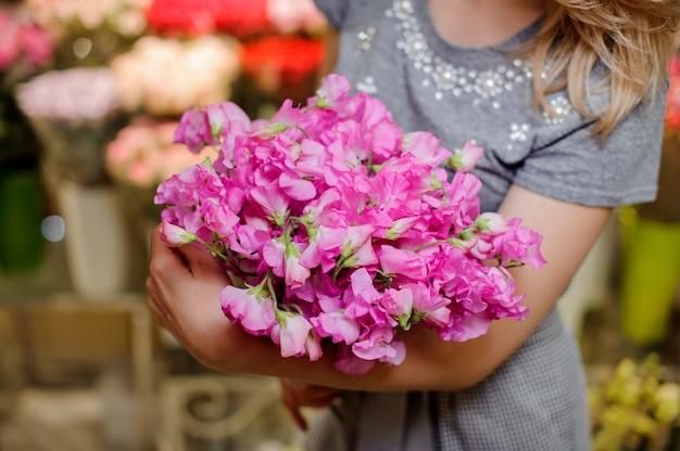 花の美しい柔らかいピンクの花束を保持している灰色のドレスの花屋