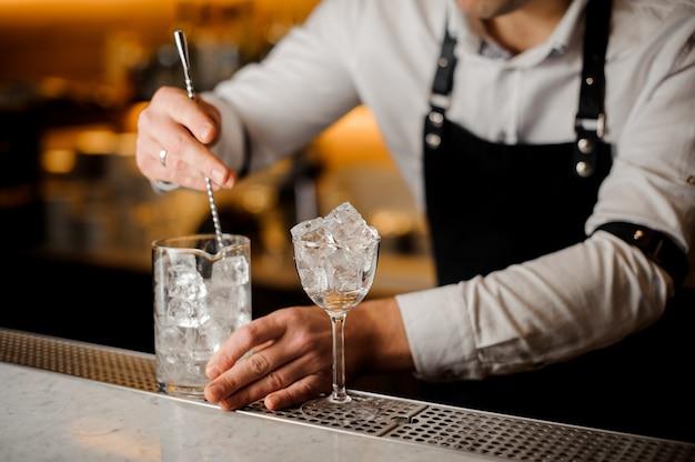 ガラスの氷を攪拌するバーテンダー