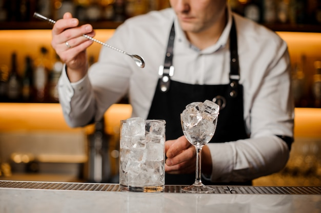 アイスキューブと長いスプーンとグラスを保持しているバーテンダー