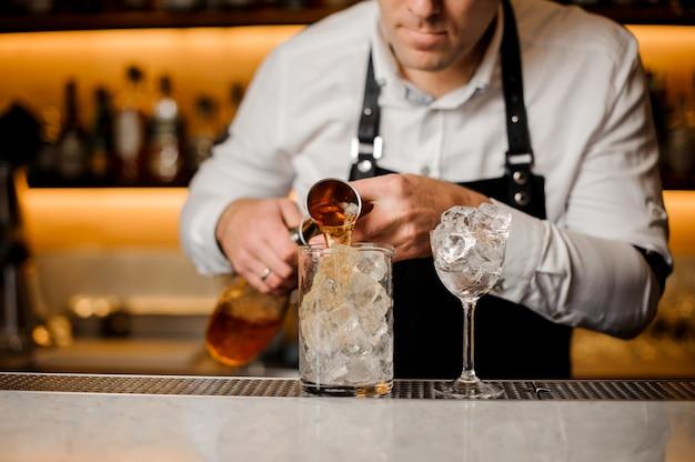 Бармен добавляет алкогольный напиток в стакан, наполненный кубиками льда