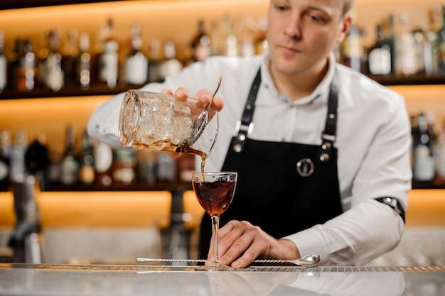 エレガントなグラスにアルコール飲料を追加する若いバーテンダー