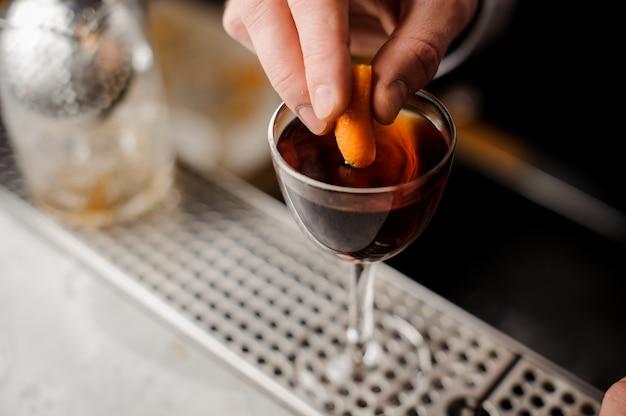 手をアルコール飲料でグラスにオレンジの皮を追加します