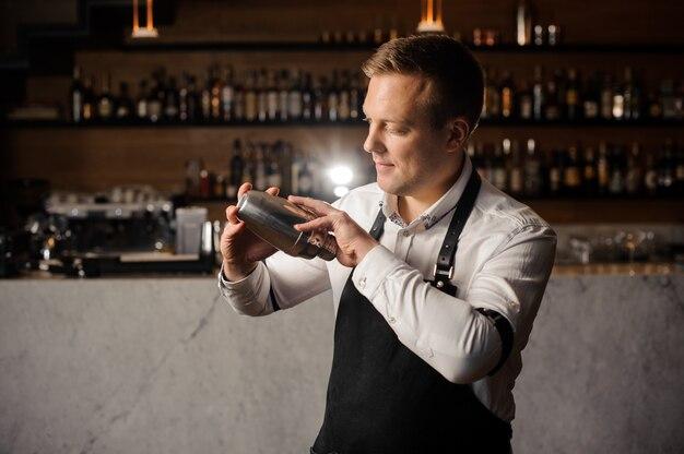 Бармен в белой рубашке и переднике держит шейкер у барной стойки