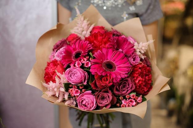 明るいピンクの花の花束を保持している女性