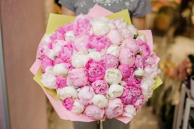ピンクの牡丹の大きな花束を保持している女性