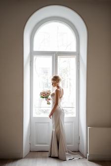 ウェディングブーケを持って素敵な白いドレスでエレガントな金髪の花嫁