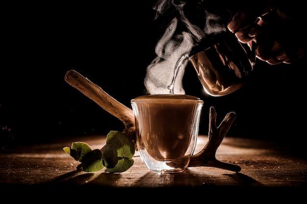 一杯のコーヒーに水を注ぐ
