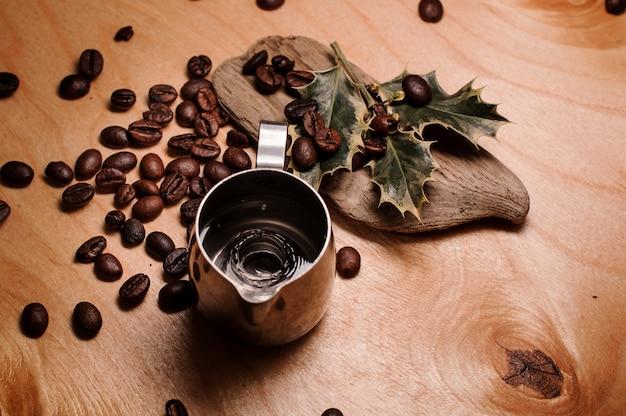 新鮮なコーヒー豆と乾燥した植物の間で水で投手