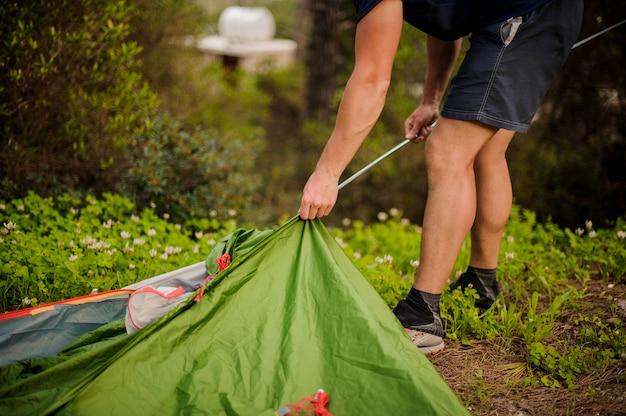 若い男は、金属製のフレームに入れて緑のテントを設定します