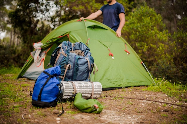 男は、ハイキング用品の近くに緑のテントを設置します