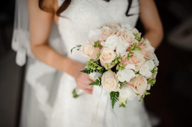 花束を持って美しい白いドレスの婚約者