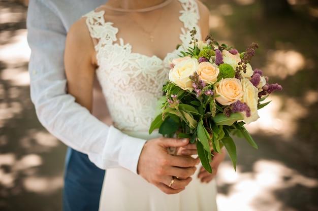 後ろから美しいウェディングドレスの花嫁を抱き締める白いシャツの新郎