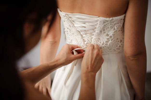 花嫁のウェディングドレスの背中に蝶結びを作る花嫁介添人