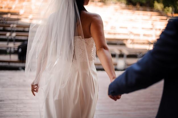 白いドレスを着た彼の美しい花嫁に続く新郎