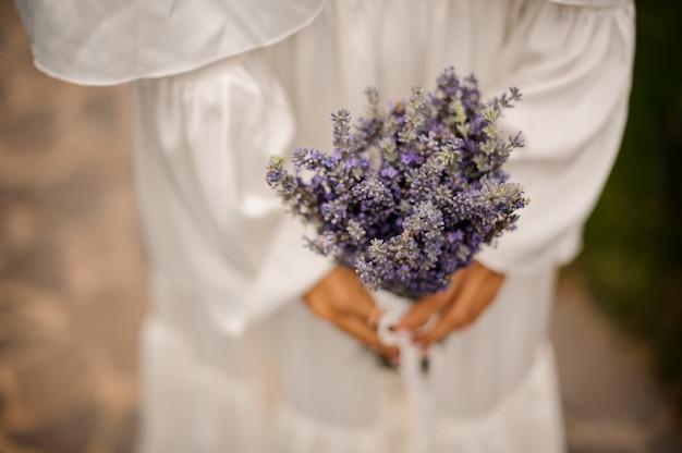 ラベンダーの花束を保持している白いドレスを着た女性
