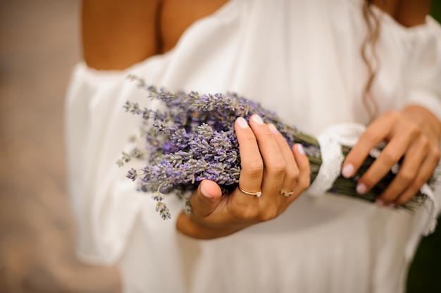 ラベンダーの花束を手で保持している白いドレスを着た女性