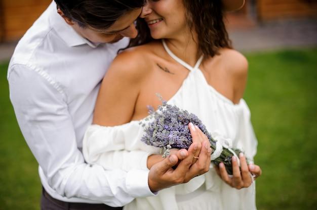 Жених в белой рубашке обнимает улыбающуюся невесту в белом платье с букетом цветов