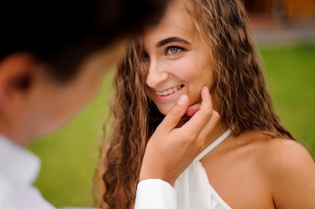 素敵な巻き毛の花嫁の美しい顔に触れる新郎