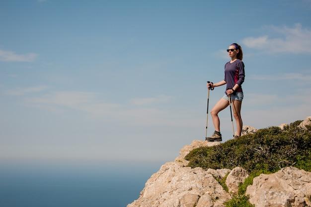 杖とショートパンツで岩の上に立っている若い女の子