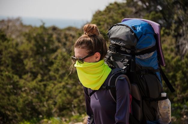 ハイキングバックパックと塵からの特別なマスクで立っている女の子