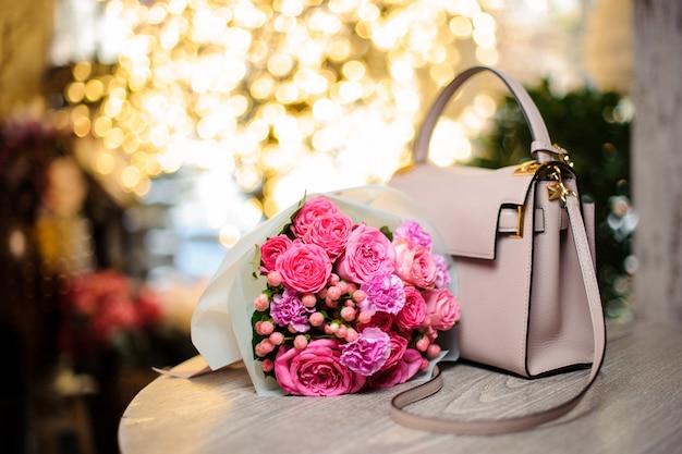 テーブルの上のスタイリッシュなハンドバッグの近くの美しいピンクの花の花束