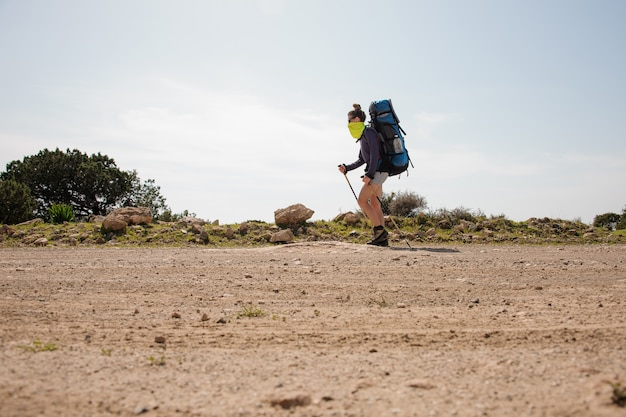 ハイキングのバックパックと塵から特別なマスクの棒で歩く若い女の子