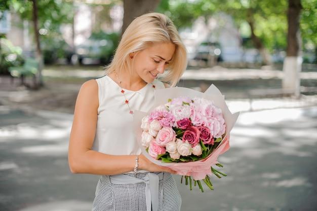 花の美しい構図を保持しているかなりブロンドの女性