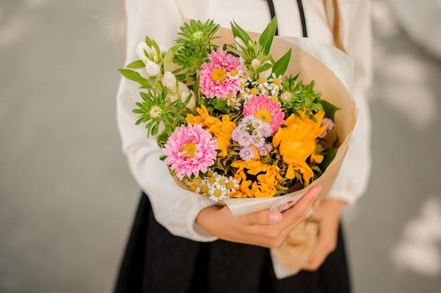 Школьница держит маленький симпатичный букет цветов